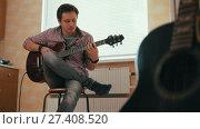 Купить «Young man composes music on the guitar and plays in the kitchen, other musical instrument in the foreground,», видеоролик № 27408520, снято 16 июля 2018 г. (c) Константин Шишкин / Фотобанк Лори