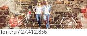 Купить «Hip young couple standing by brick wall with their bikes», фото № 27412856, снято 25 июня 2019 г. (c) Wavebreak Media / Фотобанк Лори