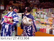 Купить «Japanese girls in bright Yukatas stopped by a souvenir store with traditional Kyoto treats and desserts on Matsubara dori street near Kiyomizu-dera. Higashiyama, Kyoto, Japan.», фото № 27413904, снято 19 ноября 2017 г. (c) age Fotostock / Фотобанк Лори