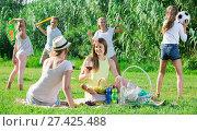 Купить «females on picnic outdoors on background with children playing active games», фото № 27425488, снято 23 августа 2017 г. (c) Яков Филимонов / Фотобанк Лори