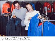 Купить «Smiling couple in sports shop to choose clothes», фото № 27425572, снято 25 октября 2017 г. (c) Яков Филимонов / Фотобанк Лори