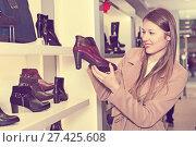 Купить «Smiling girl is choosing autumn shoes», фото № 27425608, снято 13 декабря 2017 г. (c) Яков Филимонов / Фотобанк Лори