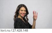 Купить «happy beautiful young woman waving hand», видеоролик № 27428148, снято 11 января 2018 г. (c) Syda Productions / Фотобанк Лори