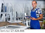 Купить «Focused workman in overalls controlling quality of assembly of plastic window in workshop», фото № 27428888, снято 19 июля 2017 г. (c) Яков Филимонов / Фотобанк Лори