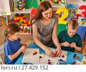 Купить «Plasticine modeling clay in children class. Teacher teaches in school.», фото № 27429152, снято 25 марта 2017 г. (c) Gennadiy Poznyakov / Фотобанк Лори