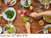 Купить «group of people eating at table with food», фото № 27461616, снято 5 октября 2017 г. (c) Syda Productions / Фотобанк Лори