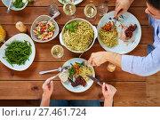 Купить «couple at table with food eating pasta and chicken», фото № 27461724, снято 5 октября 2017 г. (c) Syda Productions / Фотобанк Лори
