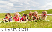 Купить «happy kids lying on meadow at red nose day», фото № 27461788, снято 13 июня 2015 г. (c) Syda Productions / Фотобанк Лори