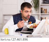 Купить «Portrait of man eating vegetable salad at table with laptop», фото № 27461896, снято 25 декабря 2017 г. (c) Яков Филимонов / Фотобанк Лори