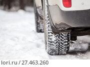 Колесо автомобиля с шипованной зимней резиной на заснеженной дороге, крупный план. Стоковое фото, фотограф Кекяляйнен Андрей / Фотобанк Лори