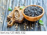 Купить «Sunflower seeds in a wooden bowl and scoop», фото № 27465132, снято 3 апреля 2017 г. (c) Марина Сапрунова / Фотобанк Лори