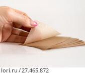 Купить «Matting cosmetic napkins to remove greasy gloss from face in hand.», фото № 27465872, снято 22 января 2018 г. (c) Володина Ольга / Фотобанк Лори