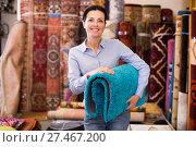 Купить «Female keep in hand colored carpet in interior shop», фото № 27467200, снято 22 ноября 2017 г. (c) Яков Филимонов / Фотобанк Лори