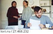 Купить «Upset guy sitting with documents while dissatisfied girl with older woman standing behind him», видеоролик № 27468232, снято 20 декабря 2017 г. (c) Яков Филимонов / Фотобанк Лори
