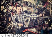 Купить «man checks bicycle handlebar in shop when choosing bike», фото № 27506048, снято 27 июня 2019 г. (c) Яков Филимонов / Фотобанк Лори