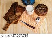 Купить «Разделочная доска, глиняный горшок с молоком, ржаной хлеб и нож на деревянном столе. Натюрморт в деревенском стиле», фото № 27507716, снято 25 января 2018 г. (c) Вадим Орлов / Фотобанк Лори