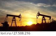 Купить «Working oil pumps silhouette against sunset», видеоролик № 27508216, снято 18 октября 2017 г. (c) Михаил Коханчиков / Фотобанк Лори