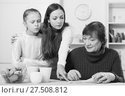 Young woman pointing to paper to elderly mother. Стоковое фото, фотограф Яков Филимонов / Фотобанк Лори