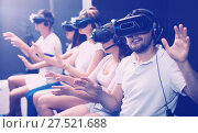 Guy is enjoying exciting movie with friends in VR glasses. Стоковое фото, фотограф Яков Филимонов / Фотобанк Лори