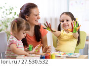 Купить «Child girl with painted hands. Kids drawing and coloring with teacher in daycare center.», фото № 27530532, снято 29 ноября 2017 г. (c) Оксана Кузьмина / Фотобанк Лори