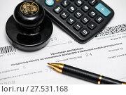 Купить «Оплата налогов. Печать предприятия, шариковая ручка, калькулятор и налоговая декларация на вменённый доход для отдельных видов деятельности», эксклюзивное фото № 27531168, снято 29 января 2018 г. (c) Игорь Низов / Фотобанк Лори