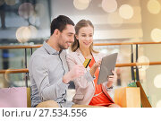 couple with tablet pc and shopping bags in mall. Стоковое фото, фотограф Syda Productions / Фотобанк Лори