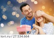 Купить «happy couple with present over lights background», фото № 27534664, снято 9 февраля 2014 г. (c) Syda Productions / Фотобанк Лори
