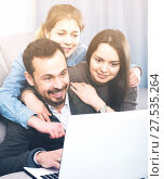 Family members enjoying booking hotel online on laptop together at home. Стоковое фото, фотограф Яков Филимонов / Фотобанк Лори