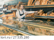 Купить «Male shop assistant demonstrating delicious loaves of bread in bakery», фото № 27535280, снято 26 января 2017 г. (c) Яков Филимонов / Фотобанк Лори