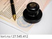 Нотариально заверенный документ, шариковая ручка и печать нотариуса на светлом фоне (2018 год). Редакционное фото, фотограф Игорь Низов / Фотобанк Лори