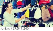 Купить «Female customer examining knit caps in sports store», фото № 27547240, снято 22 ноября 2016 г. (c) Яков Филимонов / Фотобанк Лори