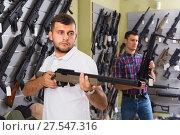 Купить «Cheerful customer man is choosing air-powered gun», фото № 27547316, снято 4 июля 2017 г. (c) Яков Филимонов / Фотобанк Лори