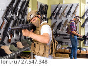 Купить «Male customers try on ammunition with weapon», фото № 27547348, снято 4 июля 2017 г. (c) Яков Филимонов / Фотобанк Лори