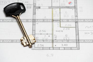 Чертёж дома на бумаге и ключ от замка квартиры