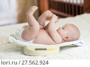 Cute little baby lying on scales at home. Стоковое фото, фотограф Оксана Кузьмина / Фотобанк Лори