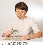 Купить «Eye problem. Woman with glasses and a magnifying glass reading a newspaper», фото № 27563076, снято 5 февраля 2018 г. (c) Юлия Бабкина / Фотобанк Лори