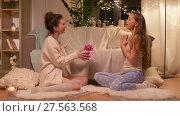 Купить «happy female friends with christmas gift at home», видеоролик № 27563568, снято 25 января 2018 г. (c) Syda Productions / Фотобанк Лори