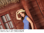 Blonde lady with straw hat near wooden house in summer time. Стоковое фото, фотограф Нелли Сабитова / Фотобанк Лори