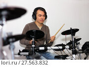 Handsome drummer with a headphones playing electronic drums in a musical classroom. Стоковое фото, фотограф Нелли Сабитова / Фотобанк Лори