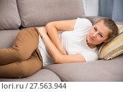 Купить «Young woman is lying with spasm because she has a stomach ache», фото № 27563944, снято 4 октября 2017 г. (c) Яков Филимонов / Фотобанк Лори