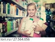 Купить «Positive girl holding shampoo and shower gel», фото № 27564056, снято 5 августа 2017 г. (c) Яков Филимонов / Фотобанк Лори