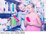 Купить «Smiling woman with girl choosing shampoo and conditioner», фото № 27564060, снято 5 августа 2017 г. (c) Яков Филимонов / Фотобанк Лори