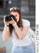 Купить «Young girl is taking photos on her camera», фото № 27564148, снято 17 мая 2017 г. (c) Яков Филимонов / Фотобанк Лори