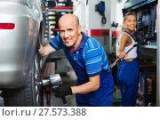 Купить «Mature male technician fitting new car tyre», фото № 27573388, снято 19 сентября 2019 г. (c) Яков Филимонов / Фотобанк Лори
