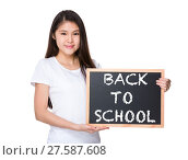 Купить «Young lady with black board and showing phrase of back to school», фото № 27587608, снято 23 июля 2018 г. (c) PantherMedia / Фотобанк Лори