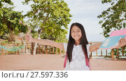 Купить «A charming philippine schoolgirl with a backpack and books in a park off the coast. A girl joyfully poses, raising her hands up with textbooks in her hands. Warm sunny day.», видеоролик № 27597336, снято 24 января 2018 г. (c) Mikhail Davidovich / Фотобанк Лори