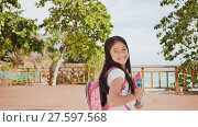 Купить «A charming philippine schoolgirl with a backpack and books in a park off the coast. A girl joyfully poses, raising her hands up with textbooks in her hands. Warm sunny day.», видеоролик № 27597568, снято 25 января 2018 г. (c) Mikhail Davidovich / Фотобанк Лори