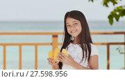 Купить «A charming philippine schoolgirl girl in a white dress and long hair positively poses with a mango in her hands. The sun. The blue ocean. Childhood. Recreation.», видеоролик № 27598956, снято 25 января 2018 г. (c) Mikhail Davidovich / Фотобанк Лори