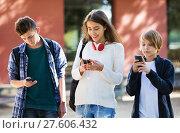Купить «Teens playing on smarthphones and listening to music», фото № 27606432, снято 28 марта 2020 г. (c) Яков Филимонов / Фотобанк Лори
