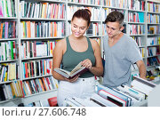 Купить «Teenagers holding book and reading new literature in shop», фото № 27606748, снято 16 сентября 2016 г. (c) Яков Филимонов / Фотобанк Лори